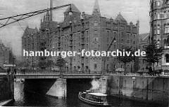 Blick über die St. Annenbrücke zum Speicherblock R - Wagen sind mit Stapeln von Säcken beladen und werden von Pferden gezogen - re. sitzt ein Kutscher auf dem Bock seines leeren Wagens und wartet auf Ladung.