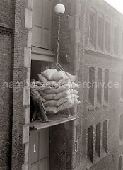 Eine Hieve mit Kaffeesäcken wird auf dem Lagerboden von den Lagerarbeitern in Empfang genommen. Sie ziehen die Ladung in die Türöffnung, um die Säcke dann ins Lager zu transportieren; ca. 1938.