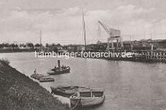 Historische Ansicht vom Hafen in Dömitz; zwei Lastkähne liegen am Ufer - weitere werden von einer Barkasse gezogen. Binnenschiffe liegen am Kai beim Hafenkran - Güterwaggons auf den Gleisen.