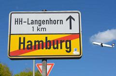 Ortsschild Ende Hamburg - HH-Langenhorn 1 km, startendes Verkehrsflugszeug.