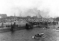 Pontons in der Elbe beim Baumwall; Ausflügler stehen dicht gedrängt auf dem Anleger und warten auf das Ausflugsschiff. Im Hintergrund die Neugotischen Türme der Speicherstadtblöcke - rechts die Einfahrt zum Sandtorhafen, dahinter die Schornste