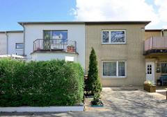 Doppelhaus mit unterschiedlicher Fassadengestaltung - weisser Anstrich / Balkon; gelber Klinker mit Stellplatz für PKW. Architekturfotos aus Hamburg Stellingen.