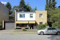Einelhaus mit Ladengeschäft und Garage - Baustil der 1960er Jahr; gelbe Klinkerfassade - Architektur in Hamburg Stellingen.