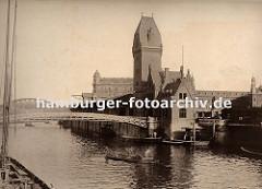 zwei Männer staken ihren Kahn mit langen Stangen über den Zollkanal in Höhe der Fussgängerbrücke Jungfernbrücke - im Hintergrund ist der Bogen der Kornhausbrücke zu erkennen. Auf dem kleinen Schiffsanleger am Kai des Kanals werden in einer hölzer
