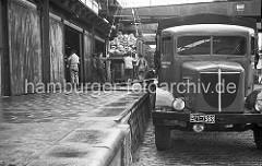 Die Ladung des Bananenfrachters wird gelöscht - eine Hieve wird von den Kaiarbeitern auf die Laderampe dirigiert - ein Lastwagen mit dem Kennzeichen der britischen Besatzungszone steht vor dem Lagerschuppen.