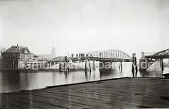 Blick auf die geöffnete Drehbrücke am Niederhafen - Holzdalben schützen die Brückenkonstruktion. Am Ufer ein Fachwerkhaus des Brückenwärters.