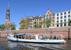 Blick vom Zollkanal zur St. Katharinenkirche und Häusern am Zippelhaus in dem Hamburger Stadtteil Altstadt. Eine Barkasse fährt mit Hamburgtouristen durch die Kanäle / Fleete der Hamburger Speicherstadt.