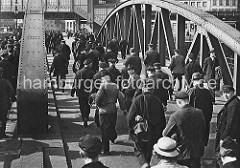 Niederbaumbrücke über den Zollkanal; Hafenarbeiter gehen nach Schichtende nach Hause - im Hintergrund das Gebäude der Hochbahnhaltestelle Baumwall.