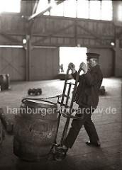 Bei einer Selbstladekarre wird das Fass beim Beladen mit einem eisernen Haken, der an einer Kette befestigt ist, auf die Handkarre gezogen. So kann der Lagerarbeiter die Tonne ohne grossen Kraftaufwand an ihren Bestimmungsort transportieren.