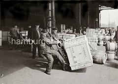 Drei Lagerarbeiter stemmen eine schwere Holzkiste auf eine Sackkarre. Im Hintergrund stehen weitere Kisten und Holzfässer im Kaischuppen und auf der Laderampe. Arbeiter arbeiten mit Handkarren im Lagerschuppen; ca. 1934.
