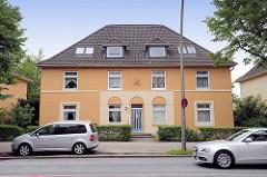 Wohnhaus im Baustil der 1930er Jahre - ockerfarbene Fassade, Strassenverkehr an der Bremer Strasse in Hamburg Eissendorf.