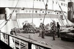 An Deck des Frachters im Hamburger Hafen bereiten die Hafenarbeiter das Löschen einer Ladung Säcke vor. Die Hieve Sackgut wird auf einer mobilen Wage gewogen, um dann mit dem Kran an Land gebracht zu werden; ca. 1934.