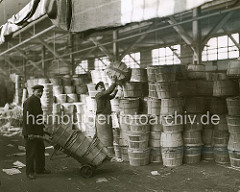 Die Arbeiter im Fruchtschuppen A am Baakenhafen, eines der vielen Hafenbecken und Kaianlagen des Hamburger Hafens, transportieren die Fässer mit Sackkarren vom Hafenkai zum Stauraum. Dort wird die empfindlichen Fracht von Hand gestapelt; ca. 1930
