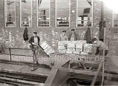 Die Hieve Apfelsinenkisten ist auf der Galerie des Fruchtschuppens abgesetzt - und das Ladegeschirr abgenommen. Von Hand werden die einzelnen Kisten aus der Partie auf die Sackkarre geladen und in den Fruchtschuppen transportiert; ca. 1930.