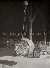 Ein Fass hängt an der Kette des Ladegeschirrs im Haken des Krans. Im Hintergrund lagern Kisten und Säcke; ca. 1930.