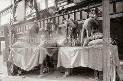 Vor dem Tor des Lagerschuppens stehen die Lagerarbeiter auf einem Podest und leeren die Säcke, die vom Frachter gelöscht wurden. An der Wand ist die Laufschiene der Halbportalkräne zu erkennen, die den Hafenkai überspannen; ca. 1934.