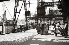 Die Ladung des Fruchtfrachters AFRICAN REEFER wird mit Kranen an Land gebracht - ein Stapel Fruchtkisten wurde vom Kran auf der Laderampe abgestellt. Hafenarbeiter sind dabei mit Sackkarren die Holzkisten in den Fruchtschuppen A.