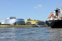 Theatergebäude an der Elbe im Hamburger Hafen im Stadtteil Steinwerder - Aufführung der Musicals Das Wunder von Bern und König der Löwen; Heck eines Frachters der aus dem Hafen ausläuft.