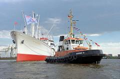 Museumsschiff CAP SAN DIEGO wendet mit Hilfe des Schleppers BUGSIER 15 auf der Elbe.
