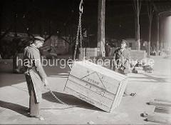 Zwei Kaiarbeiter legen an einer Holzkiste das Ladegeschirr an - eine der Ketten hängt am Haken des Hafenkrans, die Haken haben sich fest in das Verpackungsmaterial gedrückt. Die Arbeiter legen gerade eine zweite Kette zum Abtransport der Kiste an.
