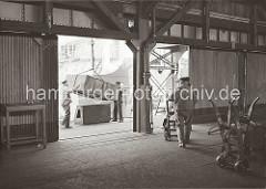 Ein Frachtschiff wird im Hamburger Hafen entladen - eine Holzkiste hängt am Haken des Hafenkrans und wird von zwei Hafenarbeitern auf einem Ladebock abgesetzt. Zwei weitere Lagerarbeiter schieben ihre Sackkarre zur Laderampe.