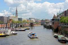 Blick über den Binnenhafen zum Zollkanal - ein Fahrgastschiff fährt in den Kanal ein - lks. die Altstadt Hamburgs, re. Gebäude der Speicherstadt.