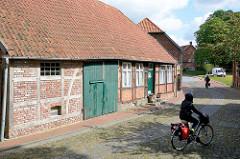 Historische Wohnhäuser an der Strasse Am Wall in Dömitz; Fachwerkhäuser - Strasse mit Kopfsteinpflaster. FahrradfahrerIn mit Satteltaschen auf Fahrradtour durch die Stadt.
