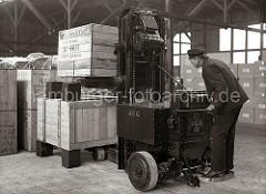 Vorsichtig stapelt ein Arbeiter mit dem Elektrohubwagen zwei Holzkisten übereinander. Die Kisten stehen auf Blöcken als Abstandshalter, damit die Gabel des AEG Elektrowagens dazwischen gefahren werden kann; ca. 1934.