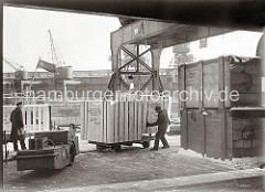 Eine große Holzkiste ist von einem sowjetischen Frachter gelöscht worden, dessen Flagge mit Hammer und Sichel am Heck des Frachtschiffs im Hintergrund weht.  Die Kiste hängt am Ladegeschirr des Halbportalkrans.