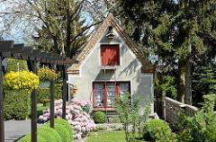 Gartenhaus mit Holzluke und Metallleiter - runder Buchsbaum, blühender Rhododendron. Fotos aus Dömitz, Landkreis Ludwigslust Pachim.
