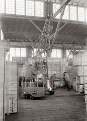 Mit einem fahrbaren Schuppenkran der Fa. Lauchhammer transportiert der Kranführer eine große Holzkiste im Schuppen. Zwei Lagerarbeiter dirigieren die Last an ihren Platz; ca 1934.