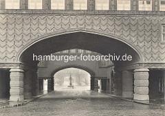 Blick durch den Torweg im Chilehaus zur Brunnenfigur am Messberghof und dem Portal der Wandrahmbrücke über den Hamburger Zollkanal.