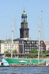 Blick über die Norderelbe zum Johannisbollwerk, an dem das Museumssschiff Rickmer Rickmers liegt - zwischen den Masten der historischen Dreimastbark der Kirchturm der St. Michaeliskirche.