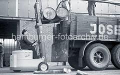 """Der Fahrer des Gabelstaplers """"Muli"""" hebt mit der Gabel des Flurfördergeräts zwei Tonnen auf die Ladefläche des Lastwagens am Togokai des Südwesthafens. Zwei Arbeiter verladen die Tonnen auf dem Lastkraftwagen; ca. 1952."""