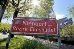 Stadtteilschild Niendorf - Bezirk Eimsbüttel; Gegenlicht, Sonne scheint durch die Bäume.