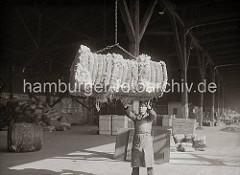 Ein Wollballen hängt im Ladegeschirr und wird von einem Hafenarbeiter am Kai angenommen. Im Hintergrund sind in dem offenen Schuppen Kisten und Säcke gelagert, ca. 1934.