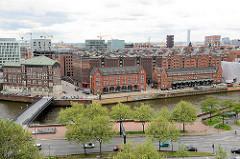 Blick vom Dach des Chilehauses auf die Speicher und Zollgebäude am Zollkanal in der Speicherstadt Hamburgs - im Hintergrund die moderne Architektur der Neubauten des neuen Hamburger Stadtteils Hafencity.