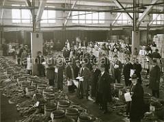 Die Fässer mit den Weintrauben sind geöffnet und die Früchte zur Begutachtung ausgestellt. Die Fruchtaukiton findet im klimatisierten Lagerschuppen 22 am Versmannkai des Baakenhafens statt; ca. 1930.