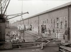 Die Hafenkrane bringen die Hieve Apfelsinenkisten zur Galerie des Fruchtschuppens - dort warten die Lagerarbeiter auf die Ladung, um die Fruchtkisten im Lagerschuppen zu verstauen. Die Halbportalkrane bewegen sich auf Schienen.