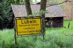 Ortsschild Lübeln, Gemeinde Küsten / Landkreis Lüchow-Dannenberg. Im Hintergrund ein Holzstall auf einer Wiese.