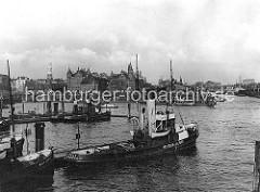 Schlepper an ihrem Liegeplatz am Baumwall; im Hintergrund die Speicherblöcke J + K, die zu beiden Seiten des Kehrwiederfleet legen. Rechts die Einfahrt zum Sandtorhafen - Frachtdampfer liegen am Kaiserkai. Am Sandtorhöft hat eine Hafenfähre an