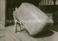 Der grosse Ballen wird vom Lagerarbeiter auf einer Sackkarre von der Laderampe aufgenommen und in das Innere des Lagerschuppens transportiert. ( ca. 1930 )