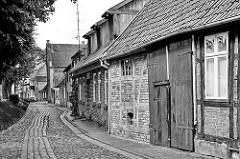 Historische Wohnhäuser an der Strasse Am Wall in Dömitz; Fachwerkhäuser - Strasse mit Kopfsteinpflaster.