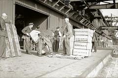 Der Kran hat eine Hieve Apfelsinenkisten auf der Laderampe eines Lagerschuppens im Hamburger Hafen abgestellt; Hafenarbeiter beladen ihre Sackkarre und transportieren die Südfrüchte an ihren Lagerplatz im Schuppen.