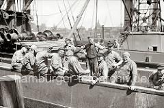 """Pause der Arbeiter auf einem Frachter - die Hafenarbeiter sitzen in der Sonne, einige rauchen, einer hat eine Flasche Bier in der Hand. Die meisten der Männer tragen einen """"Elbsegler"""", die typische Hamburger Schirmmütze mit Kordel."""