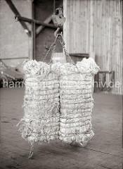 Zwei Wollballen werden von einem Ladegeschirr, dessen Haken sich in das weiche Material pressen, getragen; ca. 1934.