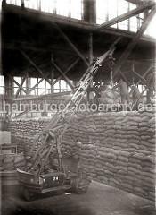 Ein beweglicher Schuppenkran hievt eine Ladung Säcke zu den Arbeitern auf dem hohen Sackstapel. Die Lagerarbeiter lösen die Hieve vom Kranhaken; ca. 1934.
