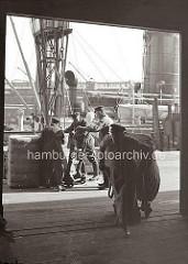 Ein Kaiarbeiter zieht seine Sackkarre mit einem schweren Ballen von der Rampe in den Lagerschuppen. Im Hintergrund sind drei Arbeiter dabei, einen der Ballen auf eine Sackkarre zu setzen; ca. 1934.