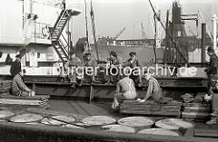 Die Schauerleute, deren Arbeit  im Stauen bzw. dem Be- und Entladen der Frachschiffe besteht machen Pause. Sie essen Brote, die sie in Aktentaschen mitgebracht haben. Einer der Hafenarbeiter greift gerade zu seiner Thermoskanne.