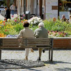Blumenrabatte am Tibarg in Hamburg Niendorf - Frühlingsblumen; Holzbank in der Sonne.